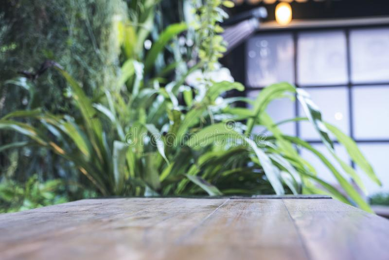 Κλείστε επάνω την εικόνα ενός ξύλινου πίνακα με τη θαμπάδα bokeh της πράσινης φύσης στοκ εικόνα