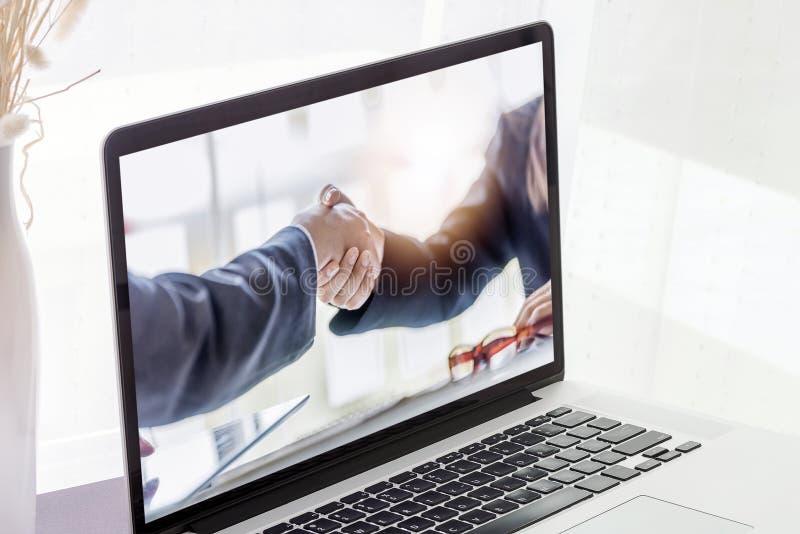 Κλείστε επάνω την εικόνα του lap-top με την εικόνα ο χειραψιών businesspeople στοκ εικόνες με δικαίωμα ελεύθερης χρήσης