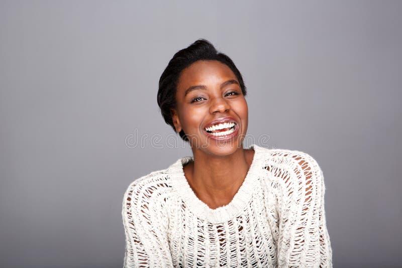 Κλείστε επάνω την ελκυστική γελώντας μαύρη γυναίκα στο άσπρο πουλόβερ στοκ εικόνα με δικαίωμα ελεύθερης χρήσης