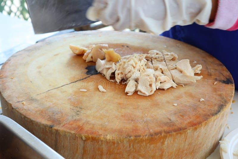 Κλείστε επάνω την εργασία του αρχιμάγειρα στην κουζίνα Woman& x27 τα χέρια του s τεμαχίζουν το κρέας κοτόπουλου σε έναν ξύλινο τέ στοκ εικόνα