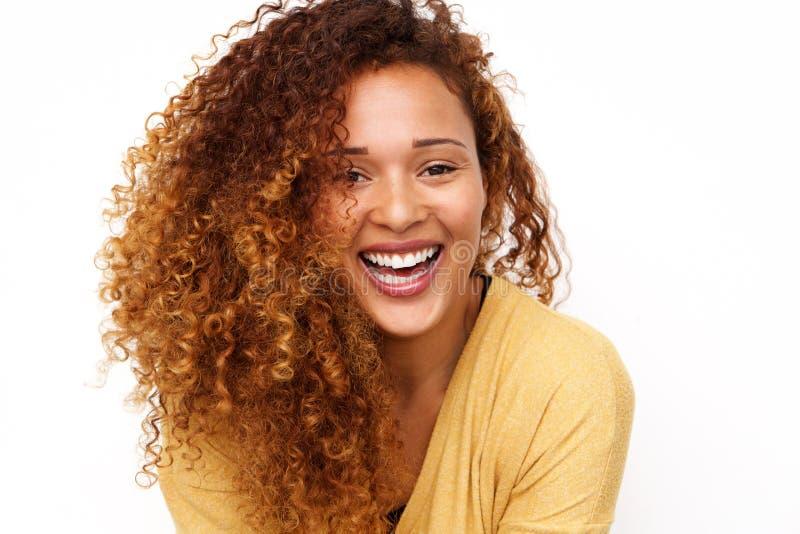 Κλείστε επάνω την ευτυχή νέα γυναίκα με τη σγουρή τρίχα που γελά στο άσπρο κλίμα στοκ εικόνες