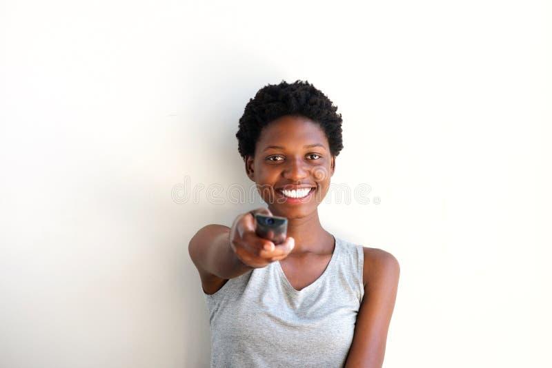 Κλείστε επάνω την εύθυμη νέα γυναίκα που κρατά τον τηλεχειρισμό και που προσέχει την τηλεόραση στο σπίτι στοκ εικόνες