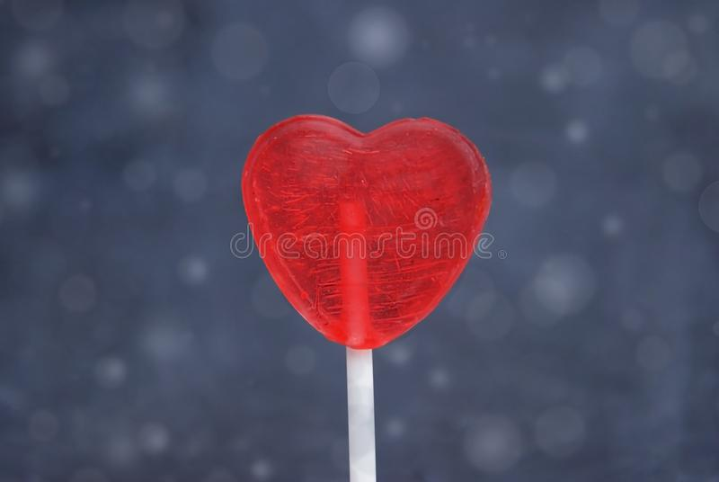 Κλείστε επάνω την κόκκινη καρδιά-μορφή Lollipop που απομονώνεται στο μπλε υπόβαθρο Bokeh Έννοια αγάπης και ημέρας βαλεντίνων ` s στοκ εικόνα
