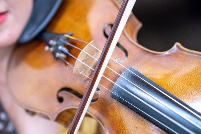 Κλείστε επάνω την ξύλινη γραμμή βιολιών ότι το κορίτσι την παίζει στοκ εικόνες