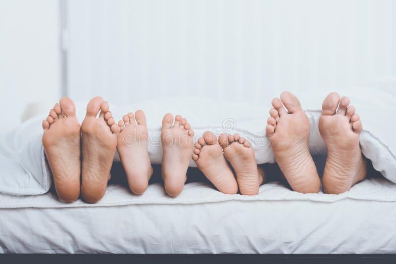 Κλείστε επάνω την οικογένεια στο κρεβάτι κάτω από την κάλυψη που παρουσιάζει πόδια στοκ εικόνες με δικαίωμα ελεύθερης χρήσης