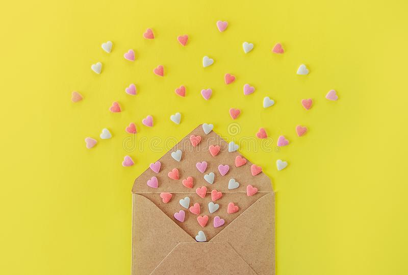 Κλείστε επάνω την πολύχρωμη μύγα καρδιών καραμελών ζάχαρης γλυκών από το φάκελο εγγράφου τεχνών στο φωτεινό κίτρινο υπόβαθρο διάν στοκ φωτογραφία με δικαίωμα ελεύθερης χρήσης