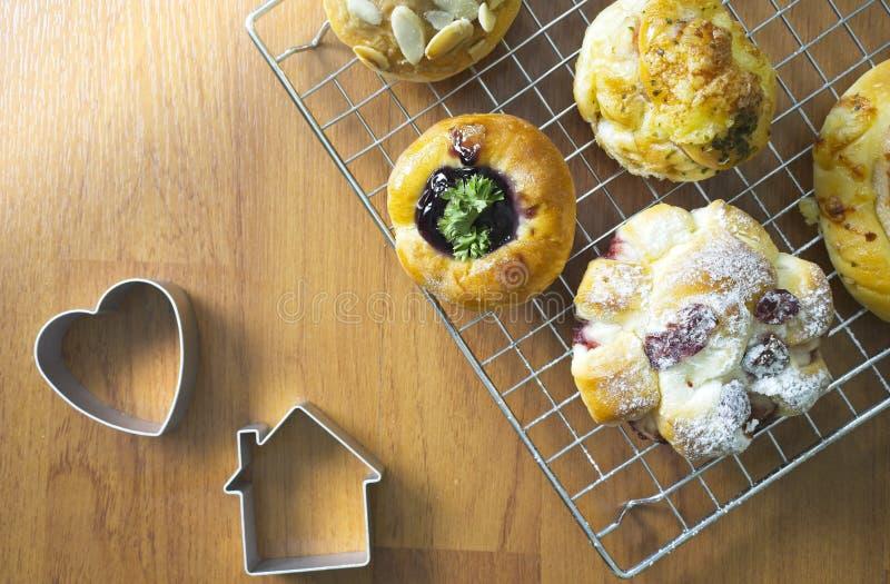 κλείστε επάνω την πρόσφατα ψημένη δανική ζύμη στο ξύλινο υπόβαθρο, το ανάμεικτες ψωμί και τη ζύμη, διαφορετικά είδη ρόλων ψωμιού στοκ εικόνα με δικαίωμα ελεύθερης χρήσης