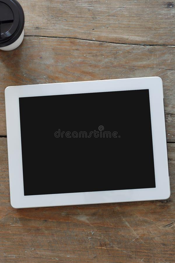 Κλείστε επάνω την ψηφιακή τοπ άποψη καφέ επιτραπέζιων φλυτζανιών ταμπλετών ξύλινη στοκ εικόνα