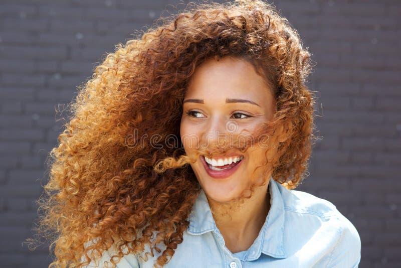 Κλείστε επάνω την όμορφη νέα γυναίκα με τη σγουρή τρίχα που χαμογελά και που κοιτάζει μακριά στοκ φωτογραφία