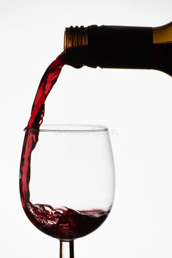 Κλείστε επάνω της έκχυσης του κόκκινου ξηρού κρασιού σε ένα γυαλί κρασιού κρυστάλλου από το πλήρες μπουκάλι του κρασιού στοκ φωτογραφία με δικαίωμα ελεύθερης χρήσης