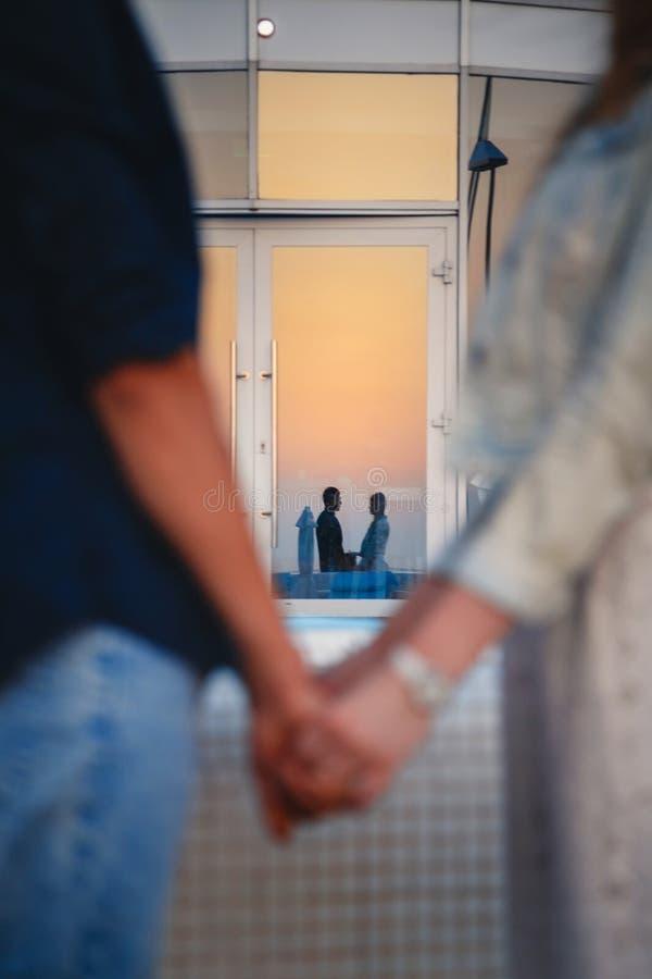 Κλείστε επάνω της αγάπης του ζεύγους που κρατά στενά τα χέρια, εστιάστε στην αντανάκλαση Έννοια χρονολόγησης και αγάπης στοκ εικόνα με δικαίωμα ελεύθερης χρήσης