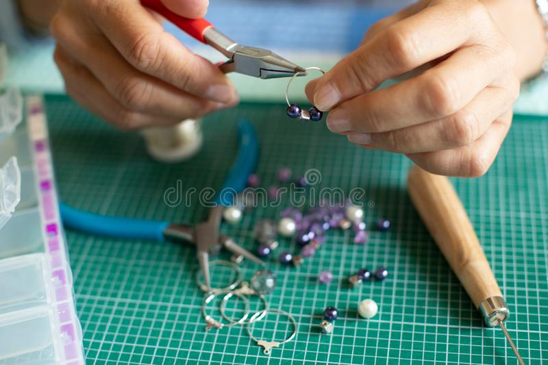Κλείστε επάνω της ανώτερης γυναίκας που κάνει τα σκουλαρίκια κοσμημάτων στο σπίτι στοκ φωτογραφίες με δικαίωμα ελεύθερης χρήσης