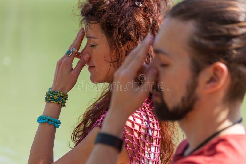 Κλείστε επάνω της γυναίκας και ο άνδρας ασκεί την υγιή έννοια τρόπου ζωής τεχνικής αναπνοής γιόγκας στοκ φωτογραφία