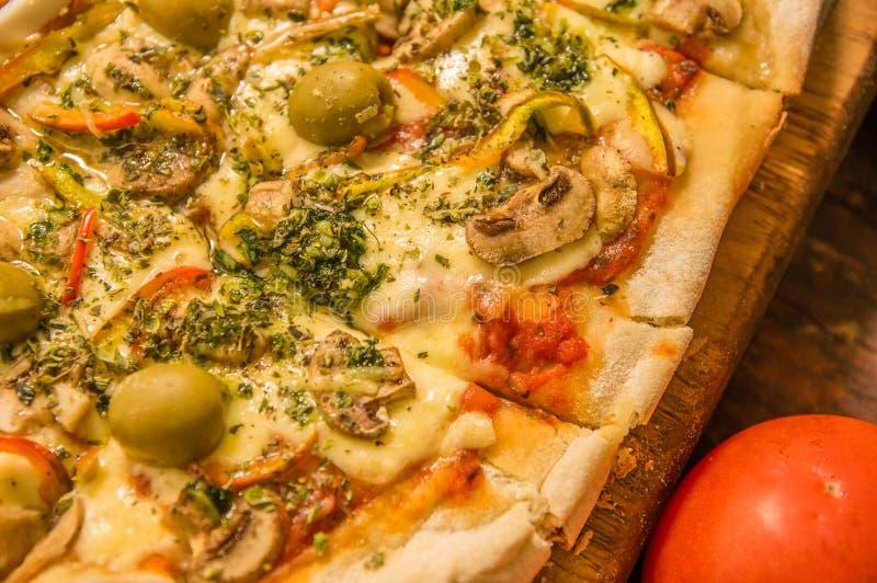 Κλείστε επάνω της εκλεκτικής εστίασης της εύγευστων πίτσας και των ντοματών στο ξύλινο επιτραπέζιο υπόβαθρο στο σπίτι έτοιμο να φ στοκ εικόνα με δικαίωμα ελεύθερης χρήσης