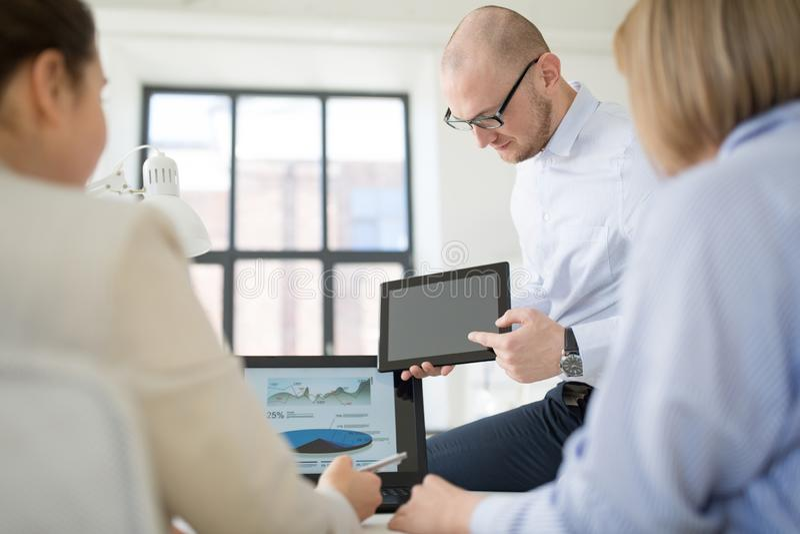 Κλείστε επάνω της επιχειρησιακής ομάδας με το PC ταμπλετών στο γραφείο στοκ φωτογραφία