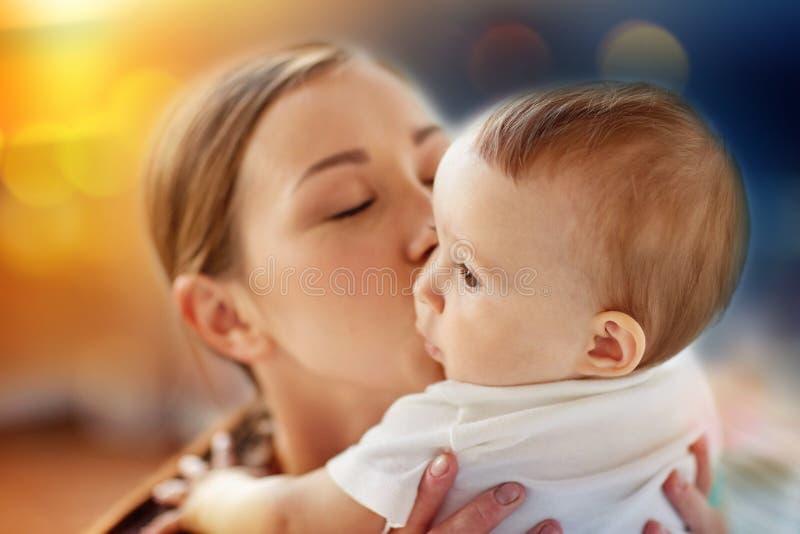 Κλείστε επάνω της ευτυχούς νέας μητέρας που φιλά λίγο μωρό στοκ εικόνες