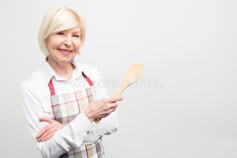 Κλείστε επάνω της ηλικιωμένης γυναίκας που επιθυμεί να περάσει το ελεύθερο χρόνο της στην κουζίνα και να μαγειρεψει τα νόστιμα τρ στοκ εικόνα