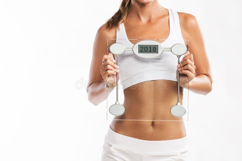 Κλείστε επάνω της κοιλίας woman's, κρατώντας μια κλίμακα βάρους με ένα έτος 2018 που γράφεται σε το στοκ εικόνα