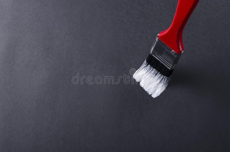 Κλείστε επάνω της κόκκινης βούρτσας χρωμάτων με τη μαύρη σκληρή τρίχα και του άσπρου χρώματος σε το Μαύρη επιφάνεια και κενό διάσ στοκ φωτογραφία με δικαίωμα ελεύθερης χρήσης