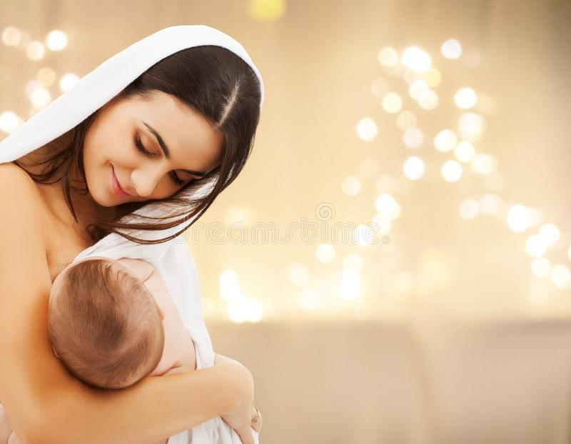 Κλείστε επάνω της μητέρας με το μωρό πέρα από τα φω'τα Χριστουγέννων στοκ εικόνες