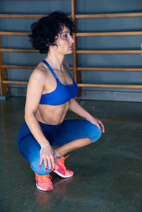 Κλείστε επάνω της νέας άσκησης γυναικών στη γυμναστική, της φθοράς sportswear, των εσωρούχων και του μπλε στηθοδέσμου, εσωτερικό  στοκ φωτογραφία με δικαίωμα ελεύθερης χρήσης