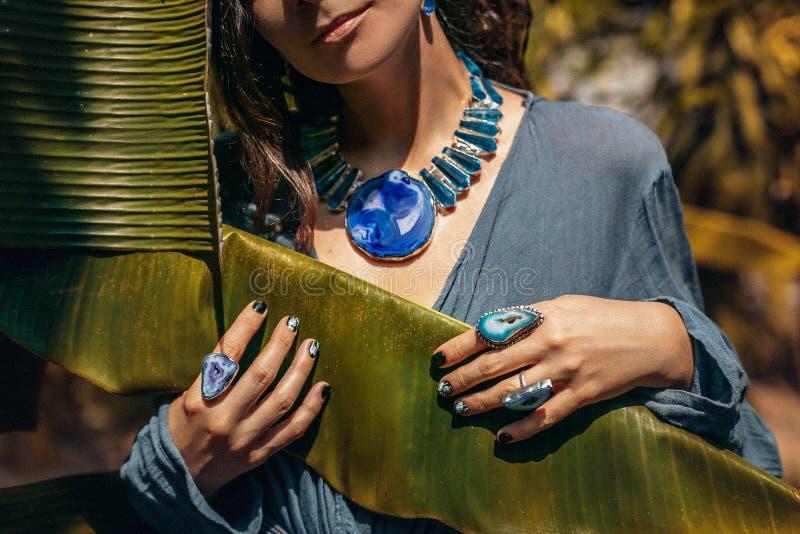 Κλείστε επάνω της νέας γυναίκας που φορά τα κοσμήματα πετρών πολύτιμων λίθων υπαίθρια στοκ εικόνες