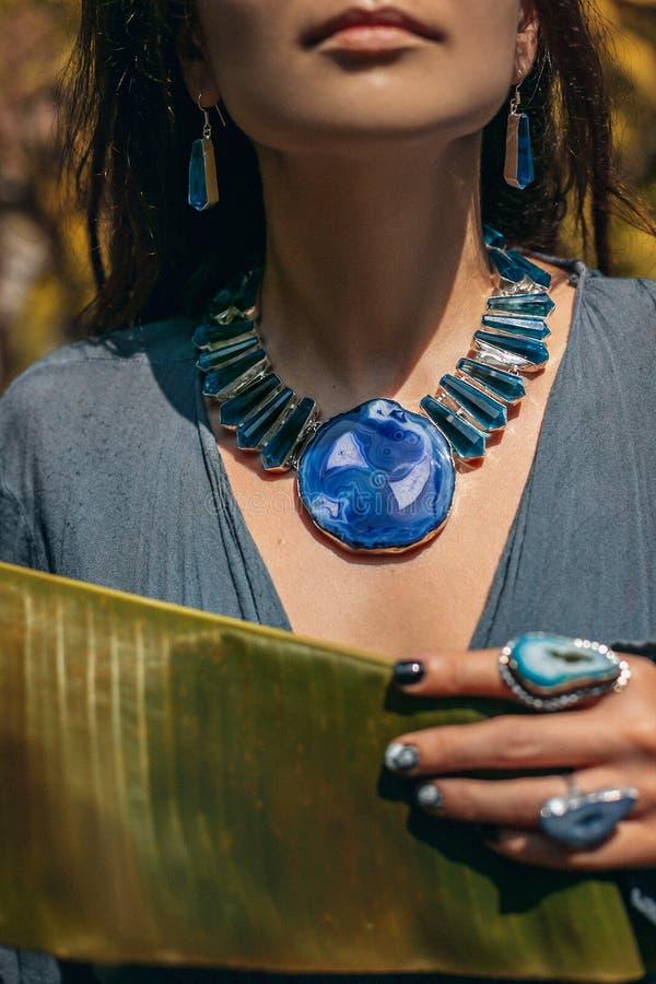 Κλείστε επάνω της νέας γυναίκας που φορά τα κοσμήματα πετρών πολύτιμων λίθων υπαίθρια στοκ εικόνα