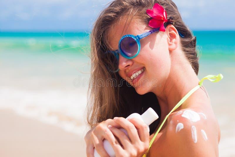 Κλείστε επάνω της νέας γυναίκας στα γυαλιά ηλίου που βάζει την κρέμα ήλιων στον ώμο στοκ εικόνες