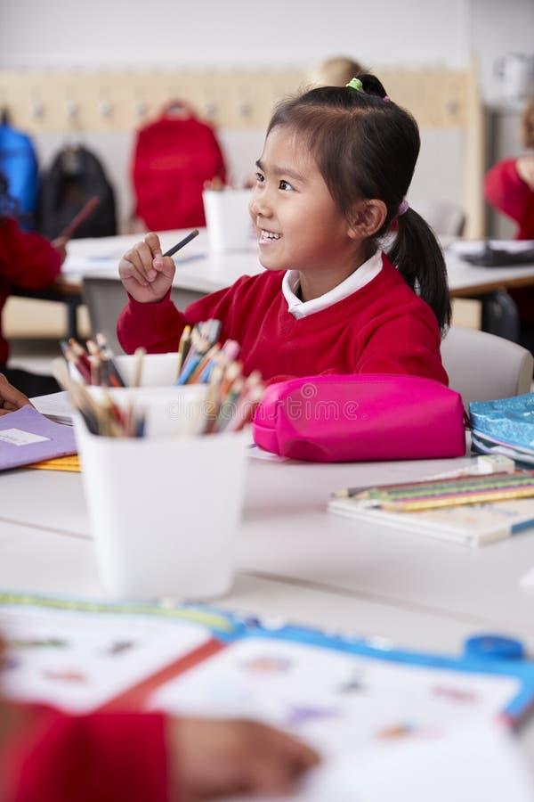 Κλείστε επάνω της νέας κινεζικής μαθήτριας που φορά τη συνεδρίαση σχολικών στολών σε ένα γραφείο σε μια σχολική τάξη νηπίων, εκλε στοκ φωτογραφίες