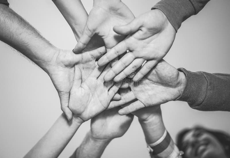 Κλείστε επάνω της νέας ομαδικής εργασίας βάζοντας τα χέρια τους μαζί για μια νέα συνεργασία - εύθυμοι φίλοι που παρακινούνται σε  στοκ εικόνα με δικαίωμα ελεύθερης χρήσης