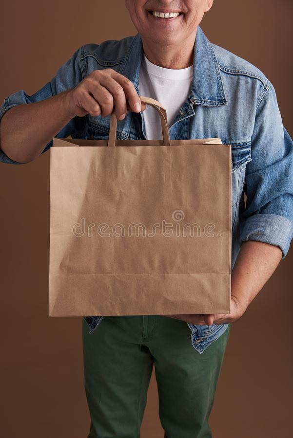 Κλείστε επάνω της τσάντας εγγράφου στα χέρια του χαμογελώντας προσώπου στοκ φωτογραφία με δικαίωμα ελεύθερης χρήσης