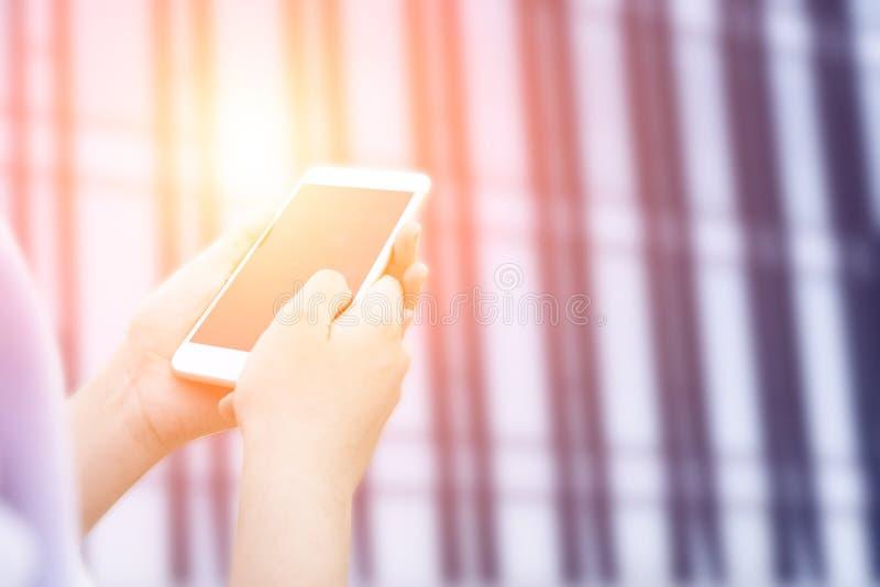 Κλείστε επάνω της χρήσης γυναικών του έξυπνου τηλεφώνου στο ηλιοβασίλεμα με το υπόβαθρο πόλεων θαμπάδων στοκ φωτογραφία