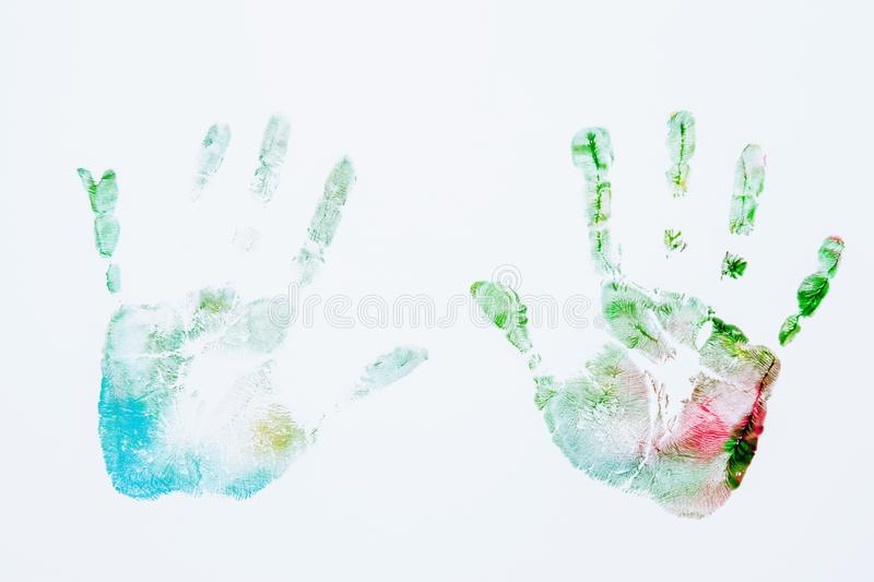 Κλείστε επάνω της χρωματισμένης τυπωμένης ύλης χεριών του ευτυχούς παιδιού στο άσπρο υπόβαθρο στοκ φωτογραφία
