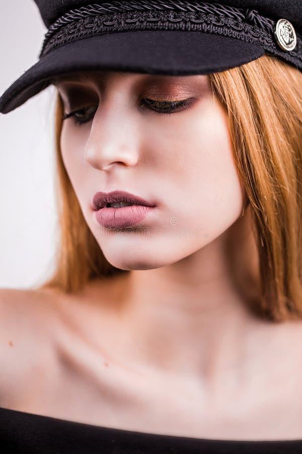 Κλείστε επάνω της όμορφης ξανθής γυναίκας με το επαγγελματικό makeup που κοιτάζει κάτω Μοντέρνο κορίτσι σε μια μαύρη ΚΑΠ στοκ φωτογραφίες με δικαίωμα ελεύθερης χρήσης