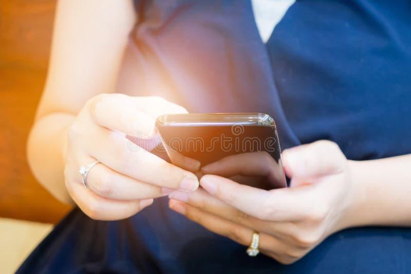 Κλείστε επάνω τη γυναίκα χρησιμοποιώντας το κινητό έξυπνο τηλέφωνο στοκ εικόνα