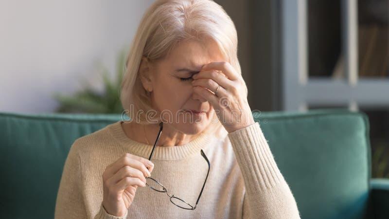 Κλείστε επάνω τη δυστυχισμένη γκρίζα μαλλιαρή ώριμη γυναίκα που πάσχει από eyestrain στοκ φωτογραφία