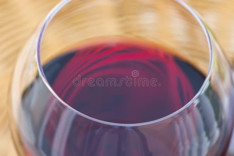 Κλείστε επάνω τη μακροεντολή του ποτηριού του κόκκινου κρασιού στον ψάθινο πίνακα ινδικού καλάμου στο πεζούλι κήπων της βίλας ή τ στοκ εικόνες