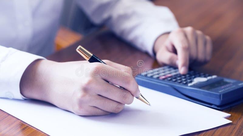Κλείστε επάνω τη νέα γυναίκα με τον υπολογιστή που μετρά και το επιχειρησιακό έγγραφο ανάλυσης στο σπίτι, χέρι γράφει σε ένα σημε στοκ φωτογραφία με δικαίωμα ελεύθερης χρήσης