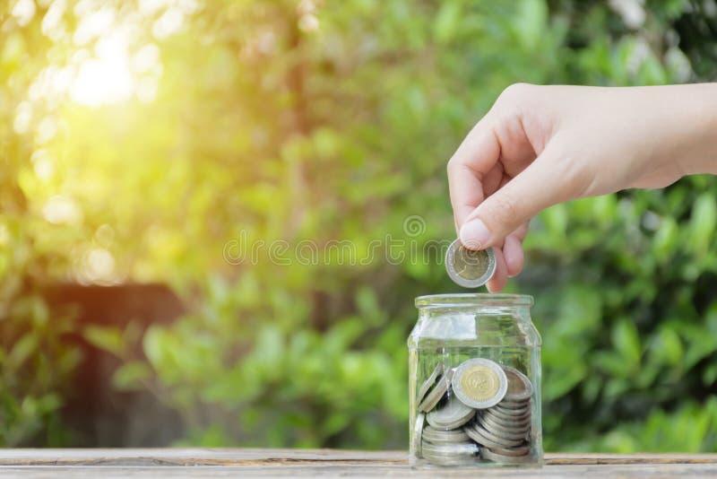 Κλείστε επάνω τη σύλληψη νομισμάτων χεριών στο μπουκάλι γυαλιού στοκ εικόνες