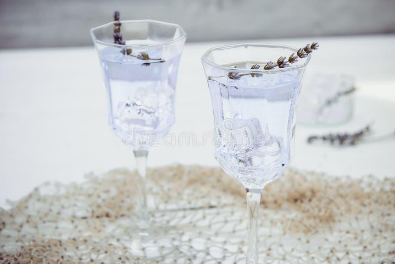 Κλείστε επάνω τη φρέσκια lavender λεμονάδα με τα λουλούδια και τους κύβους πάγου στα όμορφα ποτήρια στον άσπρο ξύλινο πίνακα r Θε στοκ εικόνες