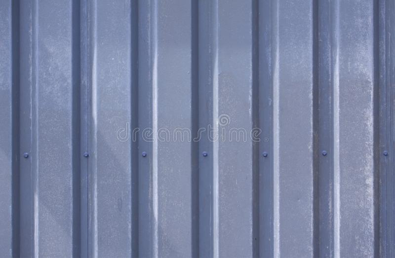 Κλείστε επάνω τη φωτογραφία μιας πρόσοψης από ένα βιομηχανικό κτήριο με τα γραφικά λωρίδες των minimalistic κάθετων μπλε ξεπερασμ στοκ φωτογραφία με δικαίωμα ελεύθερης χρήσης