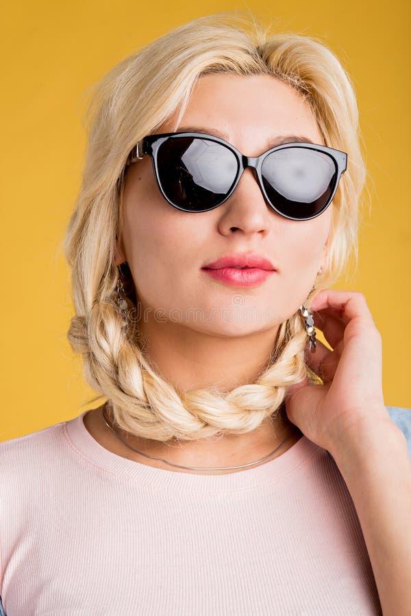 Κλείστε επάνω τη φωτογραφία της όμορφης γυναίκας στα γυαλιά ηλίου που απομονώνεται στο κίτρινο υπόβαθρο στοκ φωτογραφίες με δικαίωμα ελεύθερης χρήσης