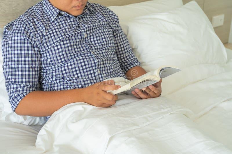 Κλείστε επάνω τη φωτογραφία του ατόμου που διαβάζει ένα βιβλίο στο κρεβάτι στοκ φωτογραφίες