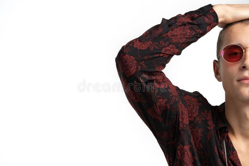 Κλείστε επάνω τη φωτογραφία του νέου ελκυστικού ατόμου στα κόκκινα γυαλιά ηλίου, που φορούν το καθιερώνον τη μόδα πουκάμισο με τη στοκ εικόνες με δικαίωμα ελεύθερης χρήσης