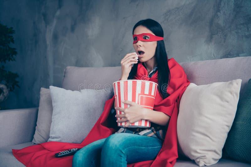 Κλείστε επάνω τη φωτογραφία όμορφη αυτή popcorn λαβής γυναικείων κοστουμιών υπερδύναμής της ο τρομακτικός κινηματογράφος καναλιών στοκ εικόνα