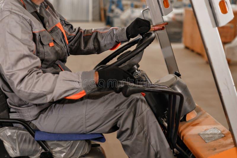 Κλείστε - επάνω τιμόνι και μοχλοί Άτομο που οδηγεί forklift μέσω μιας αποθήκης εμπορευμάτων σε ένα εργοστάσιο οδηγός σε ομοιόμορφ στοκ εικόνες