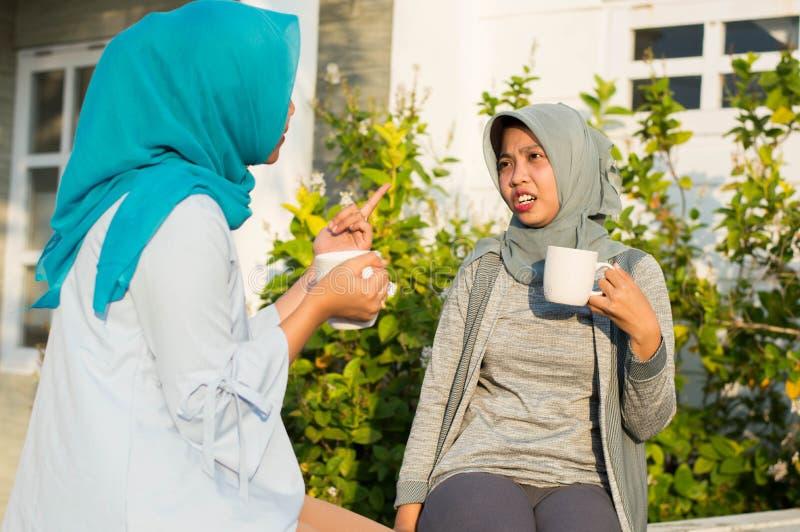 Κλείστε επάνω τις ευτυχείς βλασταημένες δύο γυναίκες hijab που πίνουν το τσάι και τον καφέ μπροστά από το σπίτι και το χαμόγελο στοκ εικόνες με δικαίωμα ελεύθερης χρήσης