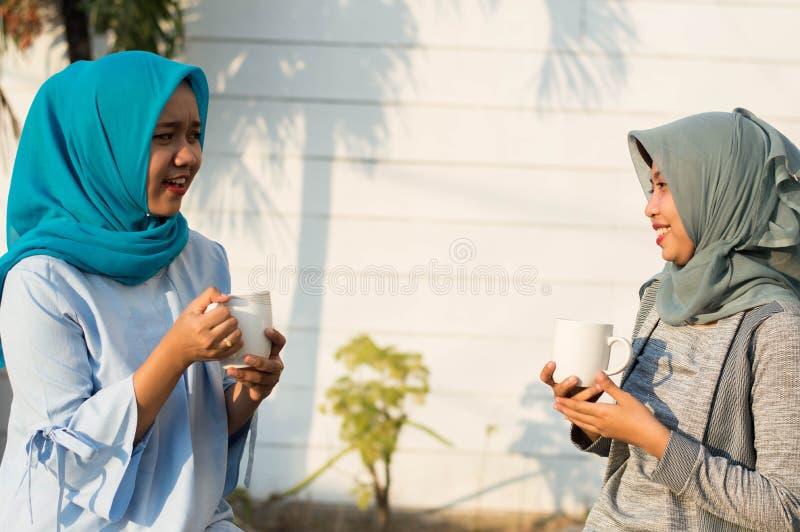 Κλείστε επάνω τις ευτυχείς βλασταημένες δύο γυναίκες hijab που πίνουν το τσάι και τον καφέ μπροστά από το σπίτι και το χαμόγελο στοκ φωτογραφία με δικαίωμα ελεύθερης χρήσης