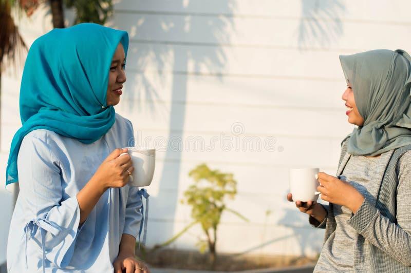 Κλείστε επάνω τις ευτυχείς βλασταημένες δύο γυναίκες hijab που πίνουν το τσάι και τον καφέ μπροστά από το σπίτι και το χαμόγελο στοκ φωτογραφίες με δικαίωμα ελεύθερης χρήσης