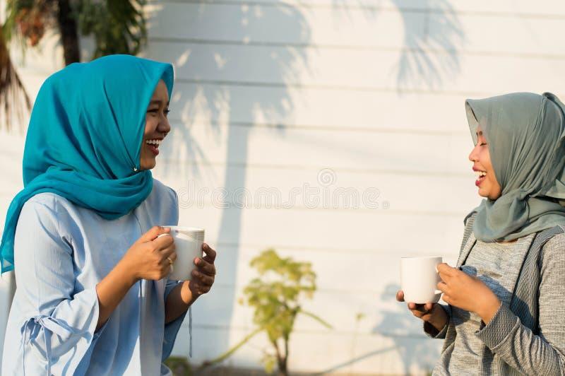 Κλείστε επάνω τις ευτυχείς βλασταημένες δύο γυναίκες hijab που πίνουν το τσάι και τον καφέ μπροστά από το σπίτι και το χαμόγελο στοκ φωτογραφία